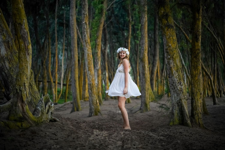 Full length of woman standing in forest