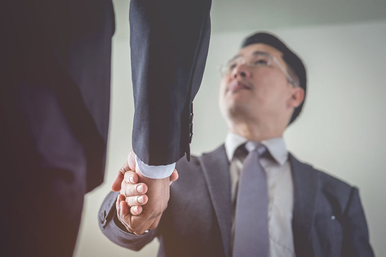 Low Angle View Of Businessmen Doing Handshake