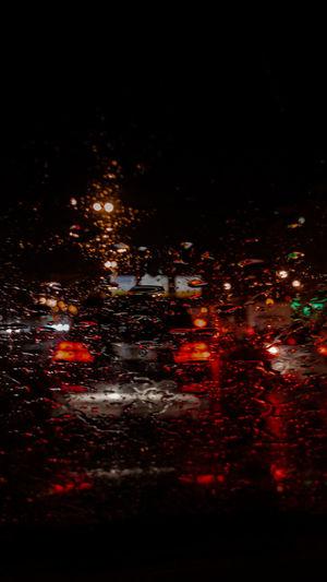 Illuminated city street seen through wet car windshield