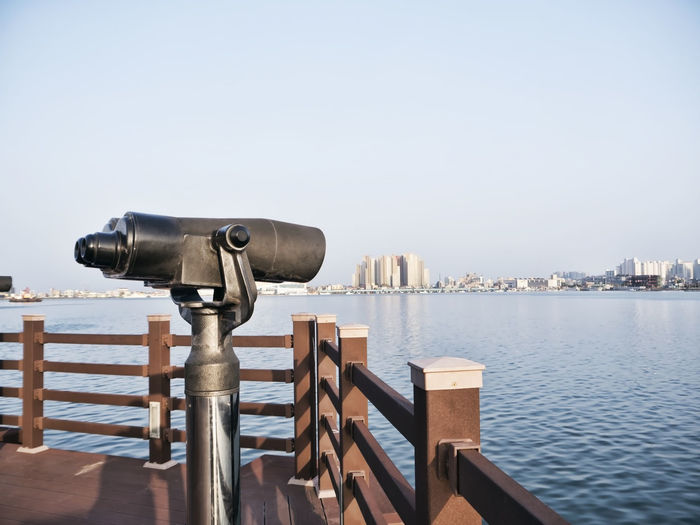 Coin-operated binoculars on wooden post by sea against clear sky