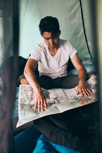 Young man looking at a map of mountain trails planning next trip on summer vacation sitting in tent