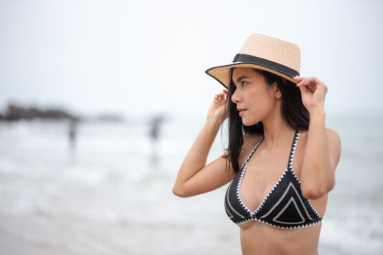 Water Young Adult One Person Clothing Young Women Hat Sea Swimwear Focus On Foreground Bikini Beauty Leisure Activity Adult Women Beautiful Woman Beach Trip Front View Vacations Sun Hat Fashion Hairstyle Outdoors