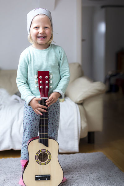 Portrait of cute girl playing acoustic guitar Acoustic Acoustic Guitar At Home Baby Beanie Blonde Childhood Couch Cute Education Fun Girl Guitar Indoors  Instrument Kindergarten Learning Lifestyle Music Musician Playing Portrait Smiling Toddler  Unfiltered