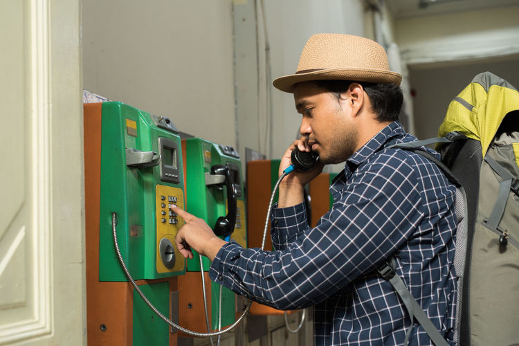 Side view of man using telephone