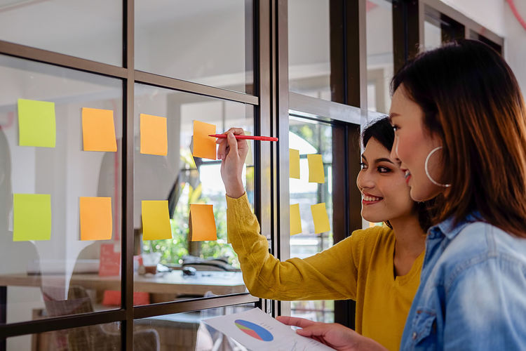 Colleagues writing on adhesive notes while standing in office