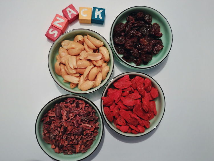 Studio Shot Directly Above Goji Berries Multi Colored Goji Yum Delicious Food And Drink Indoors  High Angle View Bowl Variation Healthy Eating Food No People Freshness White Background Ready-to-eat Close-up Raisin Peanut Cacao Snack Time! Nutrition Text