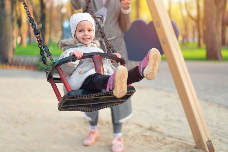Portrait of cute girl wearing warm clothing while swinging at playground