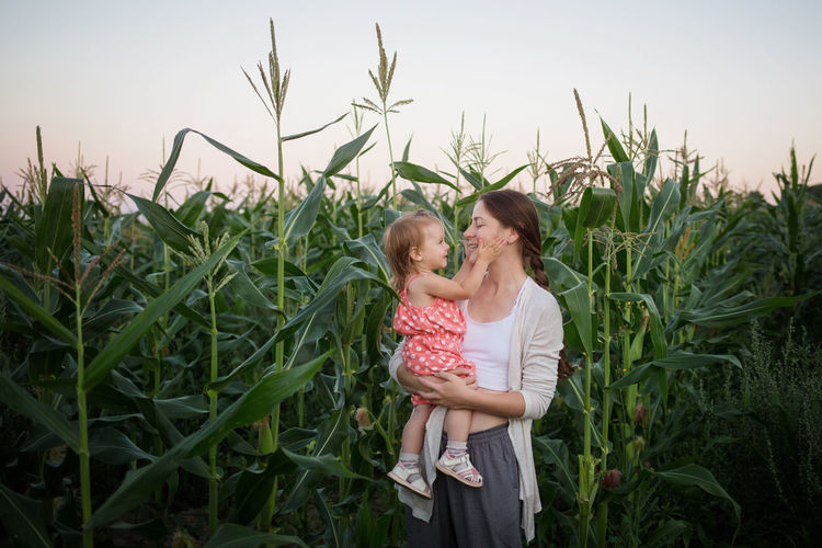 Mother and daughter on field against plants