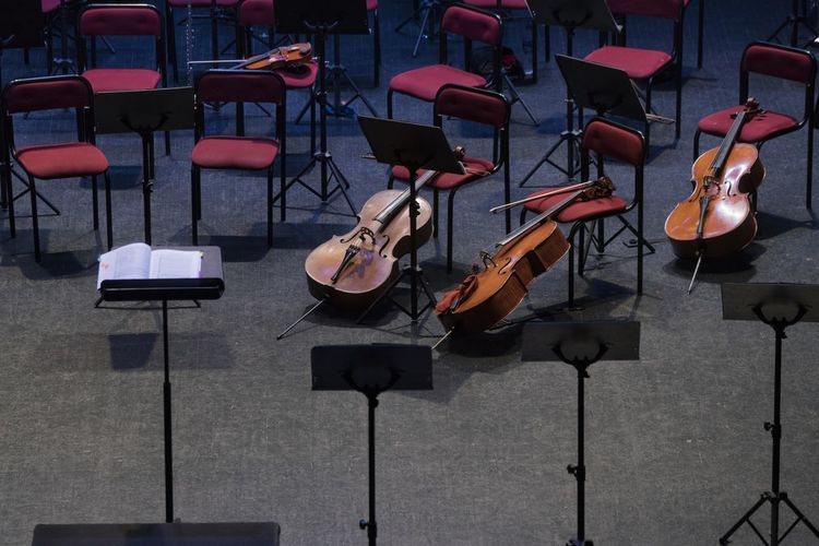 High angle view of violins and chairs in concert hall