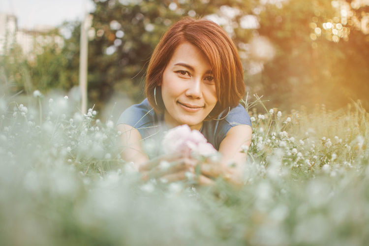 Smiling Young Woman With Flowers Lying On Grass