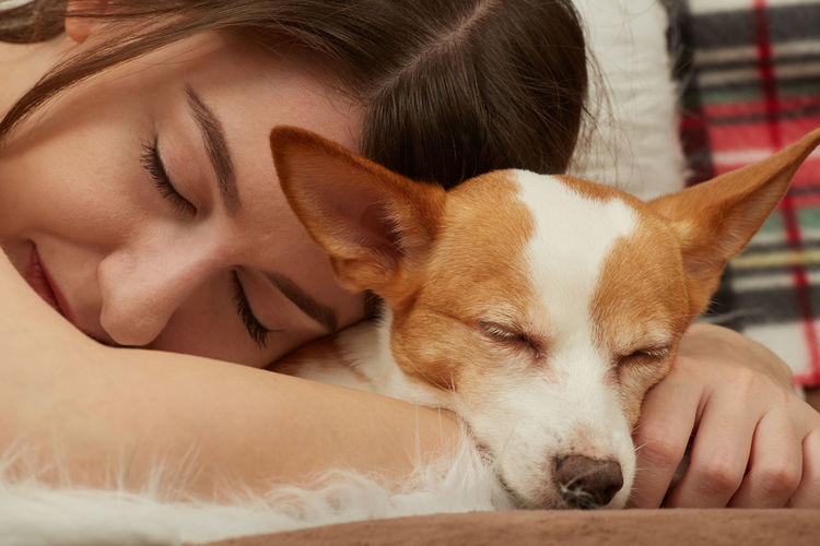 Close-up of young woman and dog sleeping on bed at home