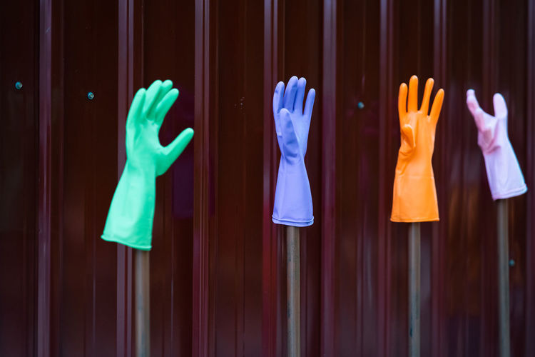 Multi colored washing up gloves against wall