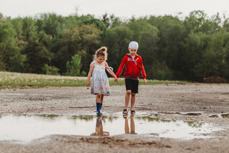 Child Childhood Full Length Two People Tree Family Water Togetherness Outdoors Real People Nature Sister Innocence Rain Casual Clothing Sibling Brother Puddle Holding Hands