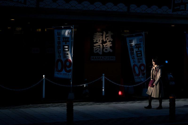 People standing on illuminated street at night