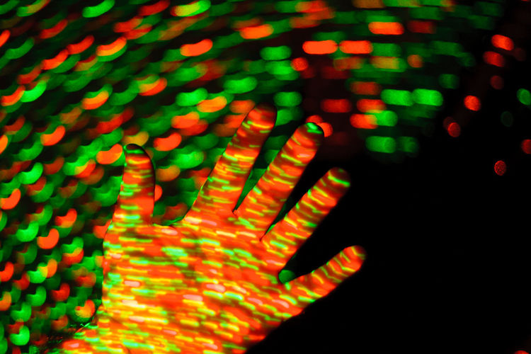Cropped hand of person with multi colored lights against black background