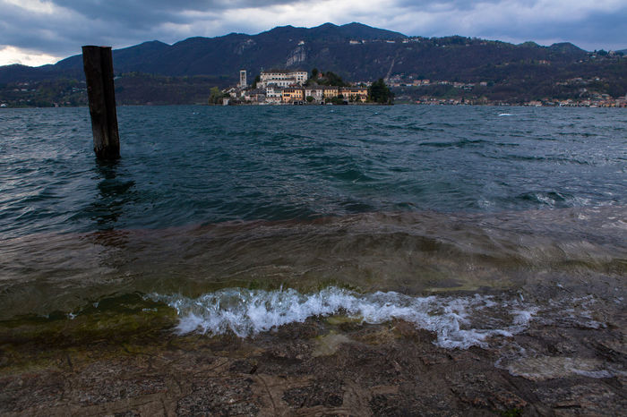 Orta San Giulio, Piedmont, Italy. Views of St. Julius' Island, in the middle of Lake Orta, with its ancient cloistered monastery, taken from the village's main square. Borghitalia Calm Clouds Historic History Island Italy Lake Lake View Lakeside Landscape Landscapes With WhiteWall Monastery Old Buildings Old Village Orta  Orta S.Giulio Orta San Giulio Piedmont Sigthtseeing Tranquil Scene Tranquility Travel Water