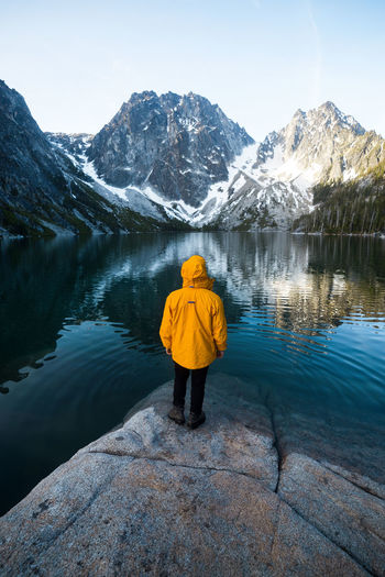 Rear view of person standing by lake against mountains and sky