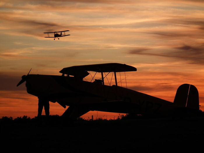 Silhouette propeller airplanes against orange sky during sunset