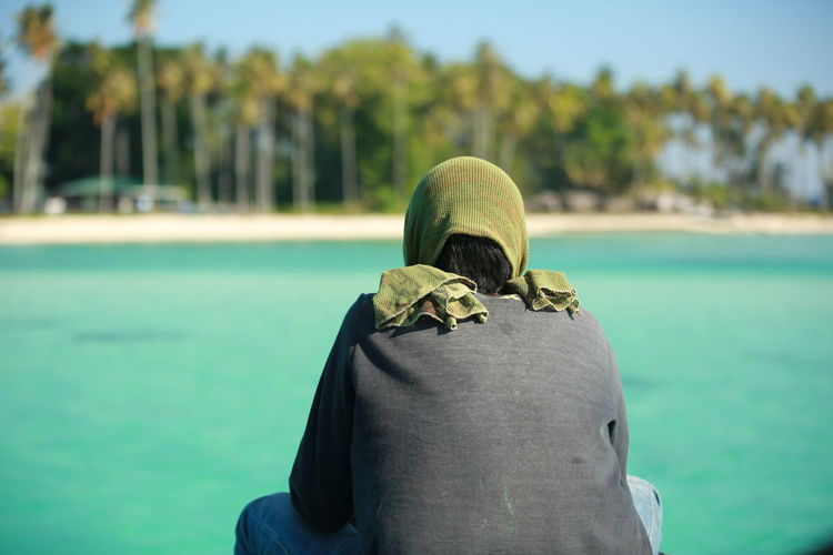 Rear view of person standing against sea