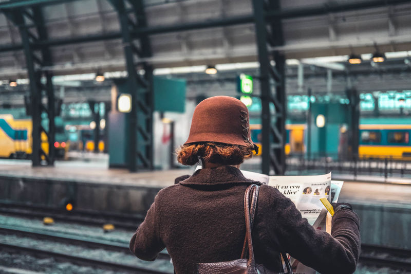Woman reading newspaper while standing at railroad station platform