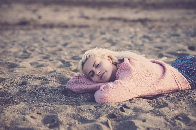 Young woman lying at beach during sunset