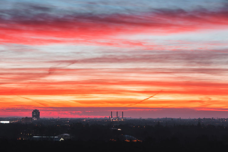 Illuminated city of berlin against dramatic sky during sunset