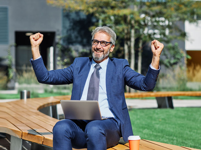 Happy businessman sitting with laptop outdoors on sunny day