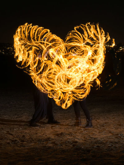 Fire dancers making heart shape on field at night