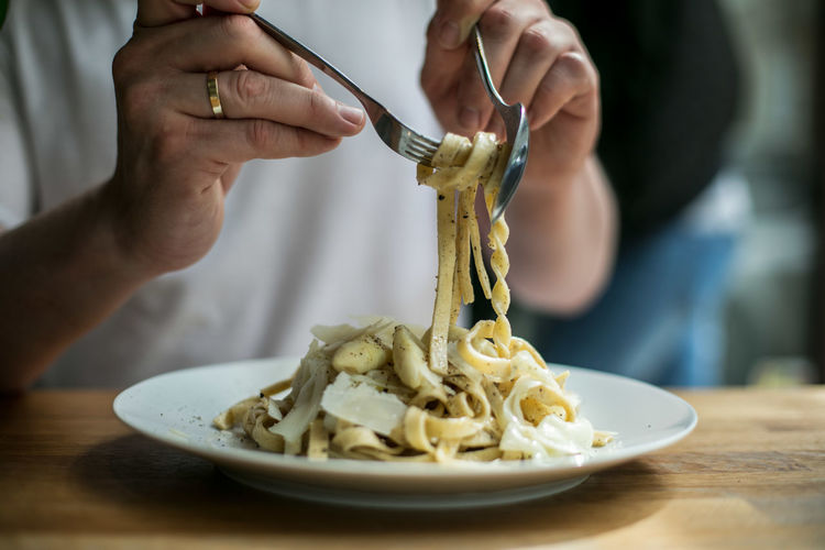 Midsection of man eating pasta
