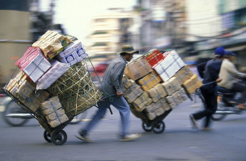 Side view of male workers carrying boxes on luggage carts at road