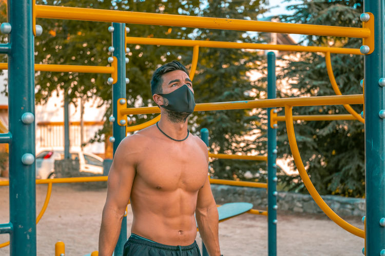 Young man wearing mask exercising outdoors