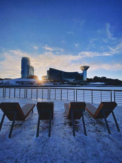 Chairs and tables against blue sky during winter