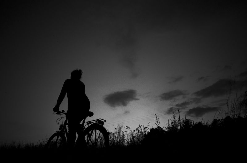 Silhouette Woman Riding Bicycle Against Sky At Night