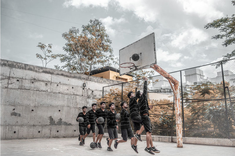 Group of people by basketball hoop against sky