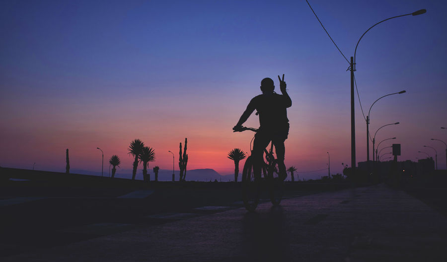 Silhouette man riding bicycle on road against sky during sunset