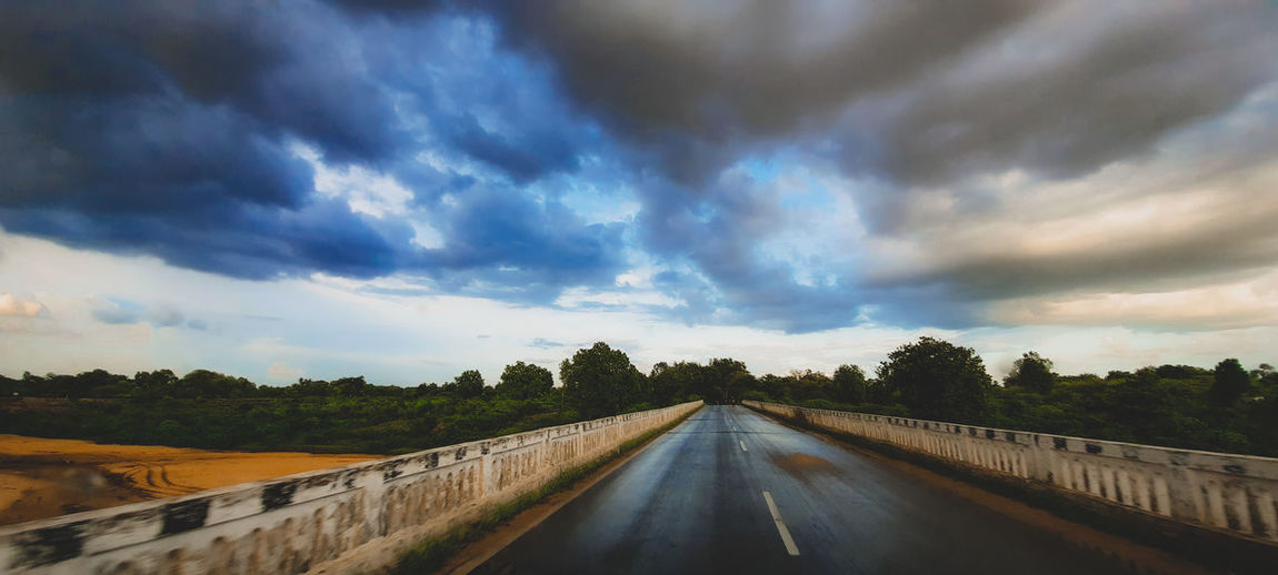 Surface level of road against cloudy sky