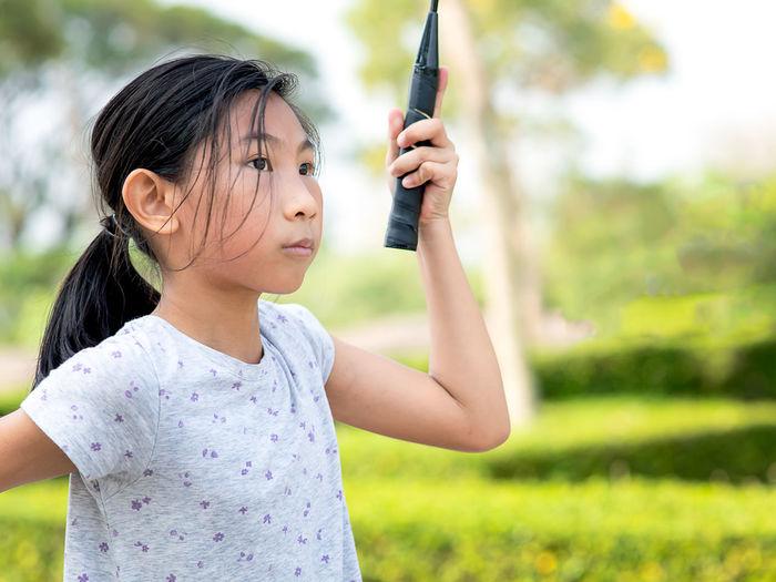 Girl looking away while playing badminton