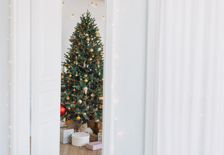 Decorated christmas tree in golden and white toys with the gift boxes from door at bright interior