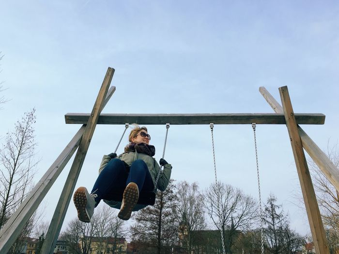Low Angle View Of Woman Enjoying On Swing Against Sky