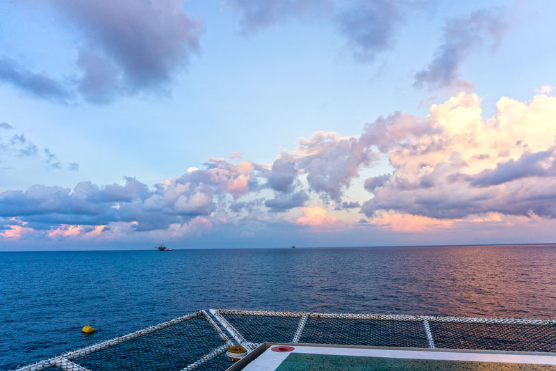 seascape oil field from a construction barge Helideck Heliport Net Deck Construction Barge Oil Rig Oil Field Petroleum Oil And Gas Industry Cloudy Ocean Calm Evening Horizon Over Water Offshore Offshore Life Platfrom Water Sea Sunset Nautical Vessel Sky Horizon Over Water Cloud - Sky Buoy Seascape