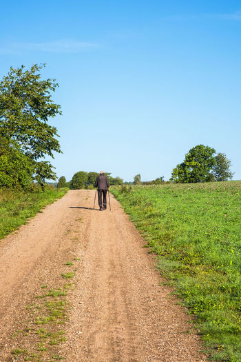 Rear view of man walking on road amidst field