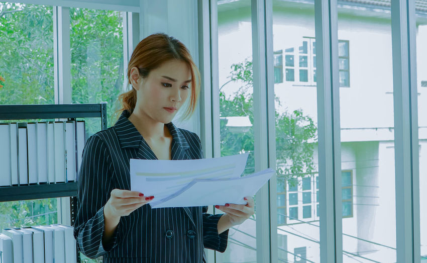 Young businesswoman holding papers at office