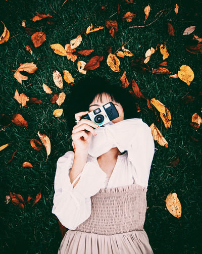 Portrait of woman photographing with autumn leaves