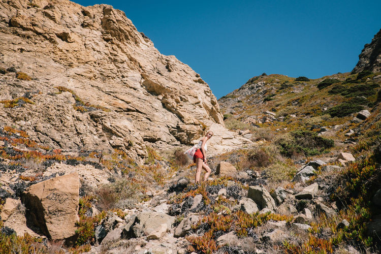 Low angle view of woman hiking on mountain against clear sky
