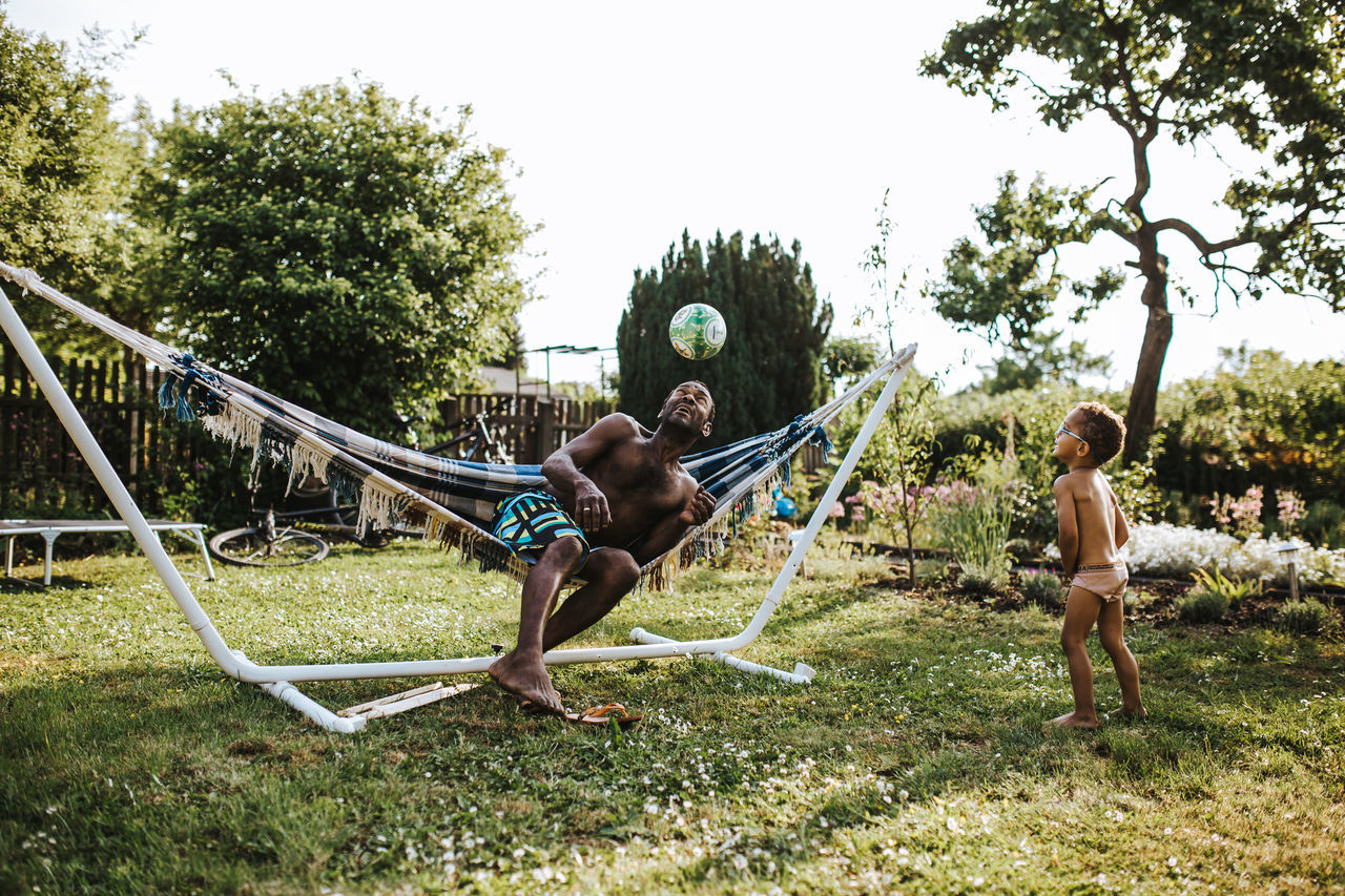 Son looking at father playing with ball in yard