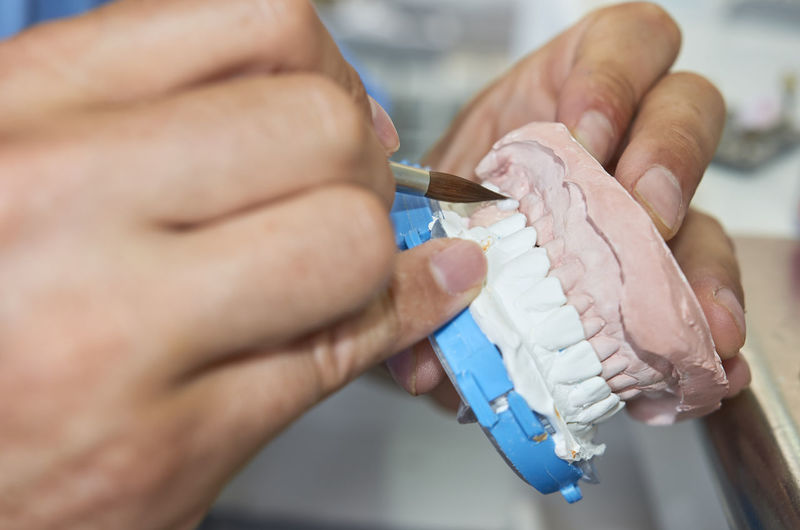 Dental technician using a brush with ceramic Crown Dental Dentist Man Mechanic Restoration Tecnology Braces Bridge Brush Cavity Ceramic Cosmetic Dental Technicians Denture Implant Laboratory Metal Professional Prosthesis Prothesis Prothodontics Technician Veneer