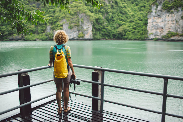 Curly Hair Girl Water Childhood Railing One Person Child Full Length Rear View Leisure Activity Nature Offspring Casual Clothing Standing Day Boys Men Tree Males  Real People Looking At View Outdoors Innocence Shorts