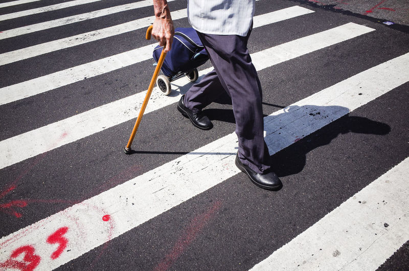 Low section of man crossing road holding a walking stick