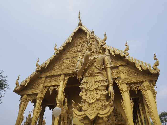 Low angle view of statues on building against sky
