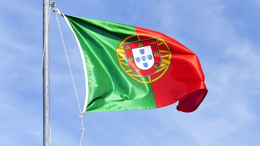 Low angle view of portugal flag against sky